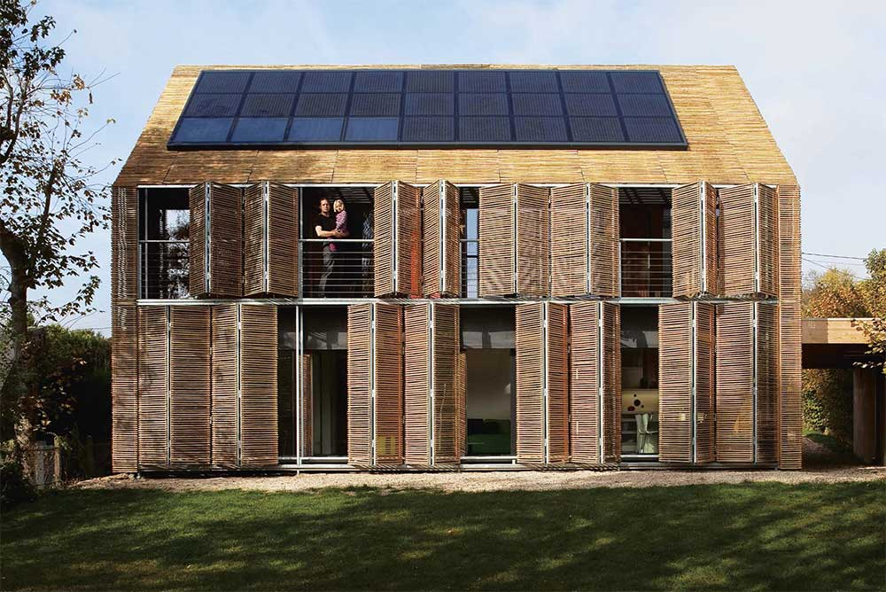 A passive house in Bessancourt, France, which features untreated bamboo cladding - including within adjustable shutters which can shade or open up the house as necessary.